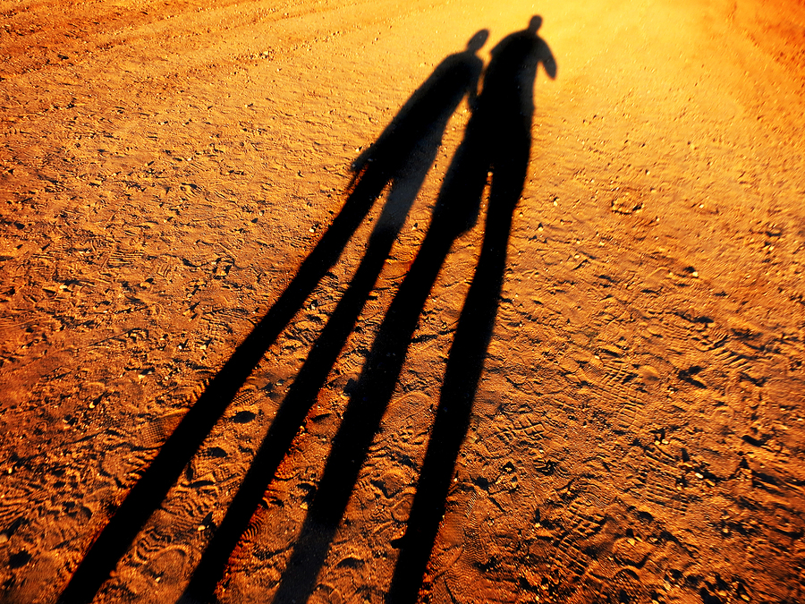 Shadow of two people holding hands walking down a dirt road toge